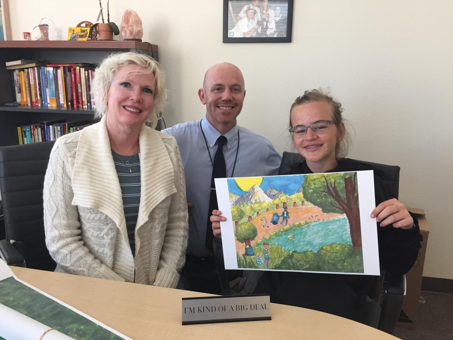 Alice Herston is joined by Principal Sheila Smith and Vice Principal Arron DeGracia as she  shows off her winning work for the Republic Service 2018 Earth Day Poster Contest!