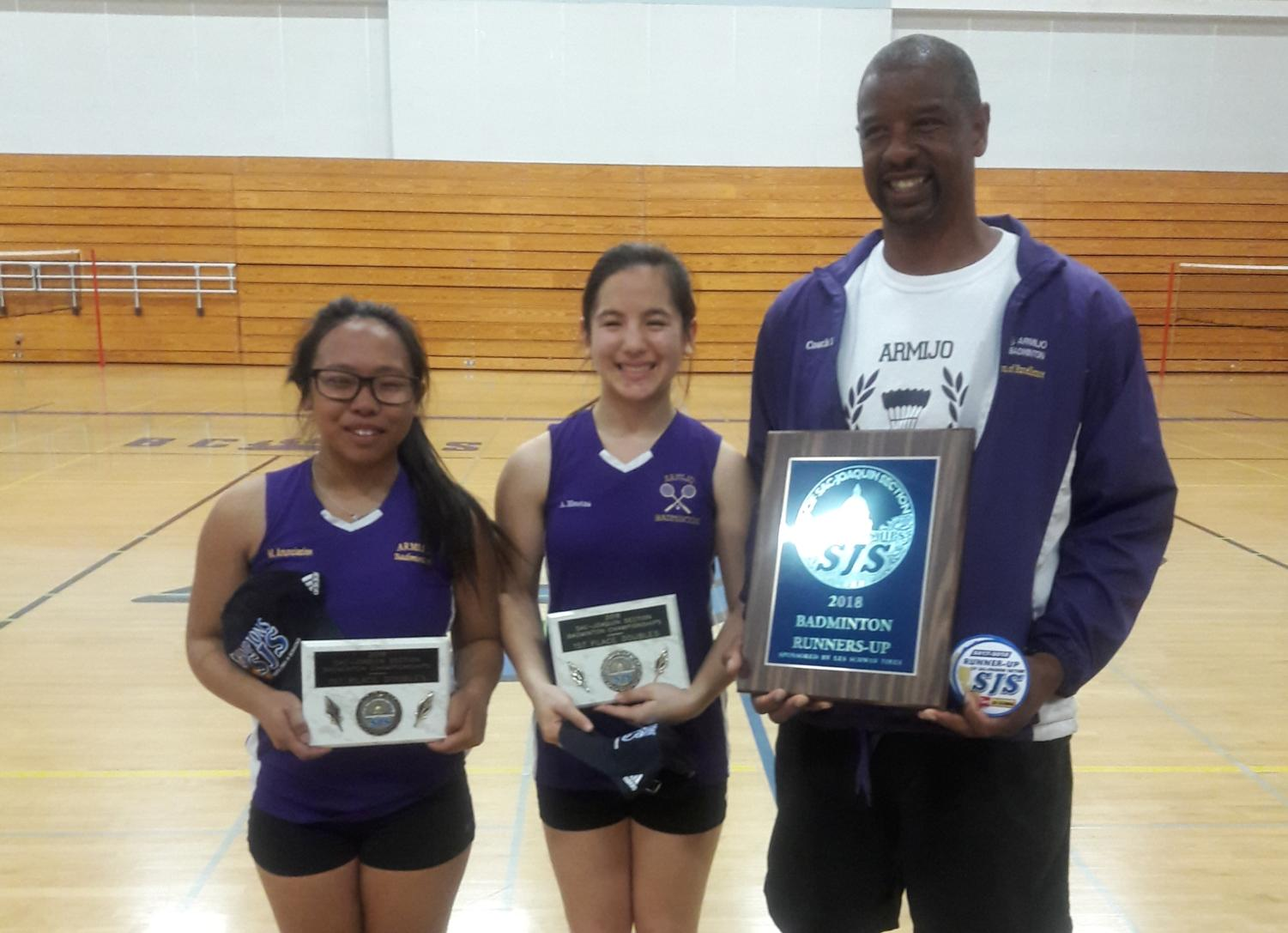 Doubles team Mhelissa and Arianna stand tall with Coach Lawrence Trigg.