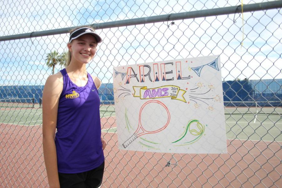 Ariel cheesing next to her senior poster.