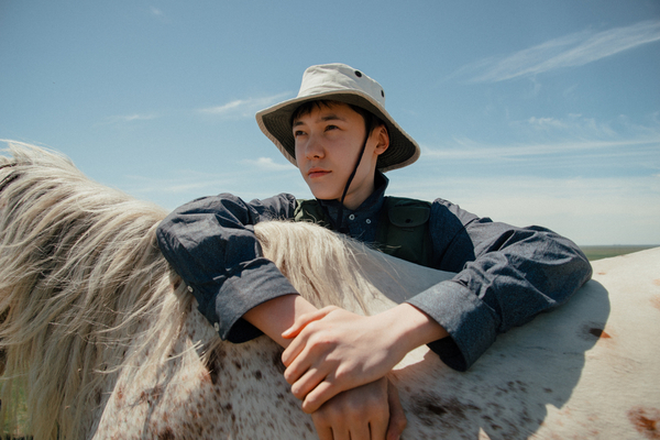 Portrait of an Asian guy with a white horse, Kazakhstan.